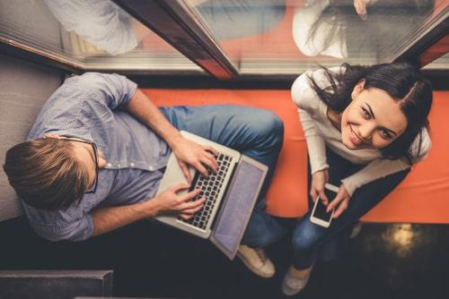 女性と男性が窓辺で電子機器を操作している画像